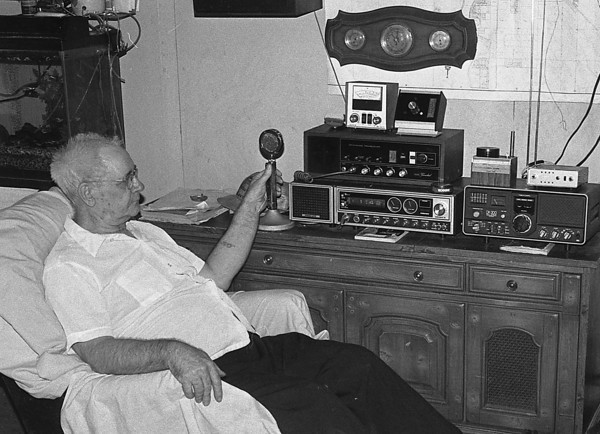 "THE GOSHEN NEWS PHOTO  January 18, 1985<br /> Performing a free service for Goshen, Art ""Grease Monkey"" Warble moniters the airways every morning on his ""President"" brand CB radio. In an average day he'll handle calls from up to 30 truckers and accidents."
