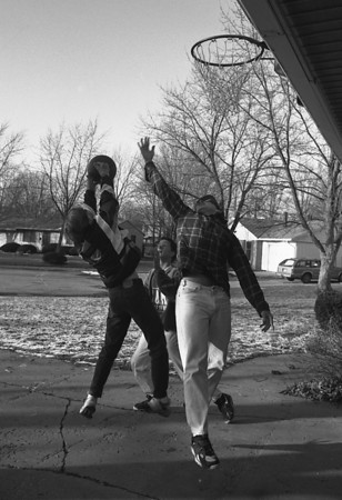 THE GOSHEN NEWS PHOTO  Back When January 23, 1993<br /> The cold weather doesn't discourage local youth from hitting the court outdoors this winter. Shawn Sherman, at left, skies for the rebound over the outstretched hand of Christian Hill while his brother, Chuck Hill, rear, looks on. The youths were playing at a neighbors house at 402 James Place in Monday's chill. The high temperature was only 28 degrees.