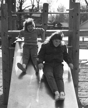 THE GOSHEN NEWS PHOTO  April 6, 1987<br /> It was a cold and damp weekend in Goshen, but that didn't stop some people from getting outside to satisfy their spring fever. Kelly Price, 16, left, and Donna Back, 12, spent some time on the playground at Parkside Elementary School in between sprinkles. Considering the massive snows dumped just east and and south of Indiana, local residents were lucky to escape with chilly weather and some light rain.