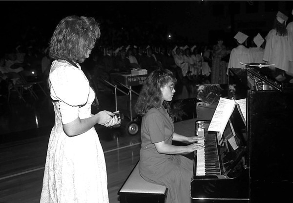 THE GOSHEN NEWS PHOTO  BACK WHEN June 1, 1991<br /> Shona Roberts points a flashlight toward the music while Ruth martin performs on the piano during Westview High School's commencement Friday night. Storms knocked out power to the school, but the ceremony continued in a dark gymnasium.