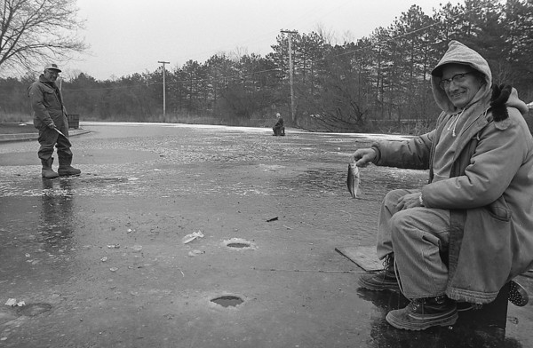 THE GOSHEN NEWS PHOTO  BACK WHEN Jan. 6, 1983<br /> In spite of warmer than normal daily temperatures, diehard fishermen have been able to find ice to fish through at a channel at Syracuse, practicing for when ice really forms on the lakes. Pictured at right is Howard Smeltzer, Syracuse, holding a small bass he pulled from the Chinese Garden channel Wednesday. With him are John McKinley, 119 W. Brooklyn, Syracuse, at left and Paul Noens, Edwardsburg, Mich., center. About half a dozen brave fishermen were perched on the three-inch ice in the channel Wednesday. Thin ice has formed on some still water, but lakes remain ice-free because of the warm weather.