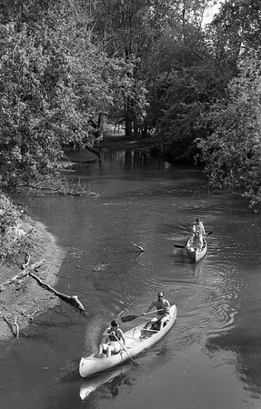 THE GOSHEN NEWS PHOTO  Back When Aug. 31, 1981<br /> The weather provided a brief respite from rain throughout Sunday afternoon before clouds moved in again in the evening. Many area residents took advantage of the day to get in some summer-type activities, including canoeing on the Elkhart River. The river became an unpopular place early in the summer when the water level was high and the current swift, causing boats to capsize. But now, the water level is just right for a leisurely canoe journey. Pictured above, two canoes move under the pedestrian bridge which connects Shanklin and New parks.