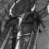 THE GOSHEN NEWS PHOTO  THE GOSHEN NEWS | DEC. 7, 1989<br /> Willie Mast and Howard Bixler work on protecting the stained glass windows of the First United Church of Christ on Fifth St. in Goshen recently. The pair ascended a lofty perch atop their ladders to seal outer storm panels which will protect the stained glass windows.