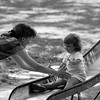 THE GOSHEN NEWS PHOTO  BACK WHEN July 6, 1990<br /> Two-year-old Kaila Swartley doesn't have to worry about getting dirty at the end of her trip down the slide because mom is waiting there to catch her. Kaila and mom, Teresa, were at Shanklin Park Thursday enjoying the sunny and warm weather. Though the Swartleys are originally from Goshen, they live in Michigan now but were in town visiting friends when they decided to take a slide break it Shanklin.