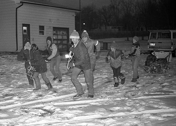 THE GOSHEN NEWS PHOTO  THE GOSHEN NEWS FEB. 14, 1983<br /> Members of the Goshen Boy Scout Troup No. 7 earned their Polar Bear Badges this weekend for roughing two cold winter nights in the outdoors. The seven area Boy Scouts who earned the badges are shown above pulling dog sledges they made out of tree parts. The boys were Terry Arrcher, 15, David Walker, 15, Bart Rich, 12, Brett Rich, 13, Todd Nisly, 10, Keith L. Wixson, 10 and Jon Zimmerman, 10. The boys slept Friday and Saturday nights in tents located near a campfire area outside the Scouit cabin, located behind the Goshen Moose Lodge. They ate pancakes, bacon and eggs, and hobo stew with deer meat all cooked over an open fire. Adult leaders who accompanied the boys were Dick Archer, Scout committee chairman and Keith E. Wixson and Dan Brimhall, assistant scoutmasters.