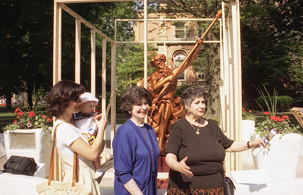 THE GOSHEN NEWS PHOTO  BACK WHEN JUNE 15, 1995<br /> Conie Polezoes, right, Elkhart, thanks Elkhart County officials for their efforts to restore the Neptune statue that was damaged last winter by vandals. The restored statue on the Elkhart County Courthouse lawn was unveiled Wednesday morning with brief comments from county officials and relatives of the statue donor. Pictured from left are Andrea Abshire with daughter Alexis; Andrea's mother, Helen Angelo, Goshen; and Conie Poleszoes. Conie and Helen are daughters of the statue donor, James Poleszoes. The 7-foot casting was broken and the trident in Neptune's hand was vandalized with the three-pointed end stolen last winter. The restored monument was uncovered in a brief ceremony Wednesday before a small crowd on the the east courthouse lawn.