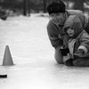 "THE GOSHEN NEWS PHOTO  THE GOSHEN NEWS | JAN. 18, 1993<br /> Three-year-old Alice Rea, bidding to be the next hockey star, gives the puck a push on the ice while mom Maria helps steady her shot during Saturday's ""Kids' Snow Day"" activities at Ox Bow Park. During the ice shuffleboard game, children pushed pucks toward a series of cones, with points awarded for the best shots."
