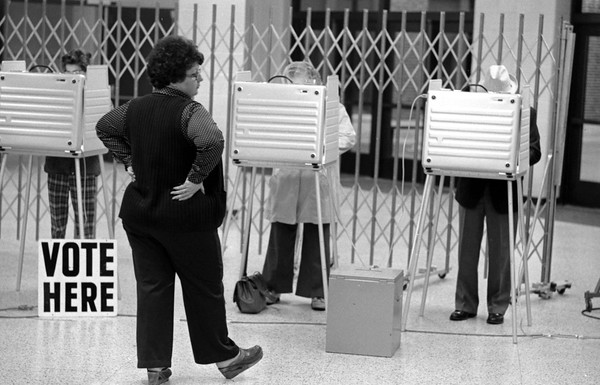 THE GOSHEN NEWS PHOTO  THE GOSHEN NEWS | NOV. 2, 1982<br /> Voter turnout was good at Goshen High School, one of the busiest polling places, where Elkhart Township Precinct 13 voted today. Above is judge Linda Kercher watching voters with the new punch card voting machines.