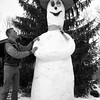 THE GOSHEN NEWS PHOTO  THE GOSHEN NEWS |  JAN. 11, 1988<br /> Bryan Keck, 17, and his father Jim created a big snowman - 10 and a half feet tall - in their yard at 14769 C.R. 8, Middlebury. Bryan is shown here looking up at the winking snowman.