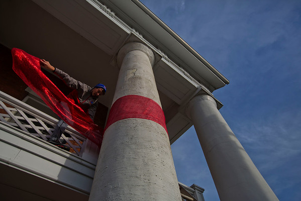 JAY YOUNG | THE GOSHEN NEWS<br /> Balancing carefully as he steps over the second floor balcony of 101N Third St., Goshen resident Burke Herr stretches out a red ribbon as he turns a white pillar into a candy cane on Tuesday morning.  Burke and his mom, Tamie, were taking advantage of the warmer weather and blue skies to hang Christmas decorations.
