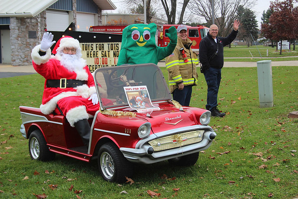 JOHN KLINE | THE GOSHEN NEWS<br /> Santa Claus made an early stop at the Elkhart Township Fire Station at the corner of Greene Road and Lincoln Avenue in Goshen Saturday as part of the department's annual Toys for Tots collection. Pictured, from left, are: Dave Swoveland (as Santa), volunteer fireman with the department; Tim Nice (as Gumby), lieutenant with the department; Matt Stanley, president of the department; and Lee Rohn, department chief.