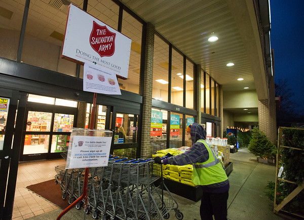 "JAY YOUNG | THE GOSHEN NEWS<br /> A Kroger employee pushes shopping carts out of the rain as he passes an empty Salvation Army kettle pole on Monday evening. Volunteers are needed to collect donations in the area. Anyone interested can register by going visiting <a href=""http://www.registertoring.com"">http://www.registertoring.com</a>."