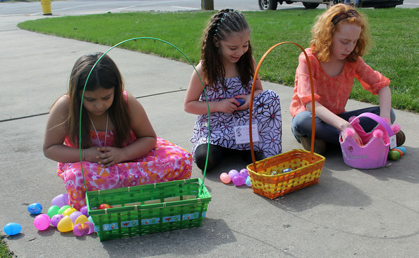 JOHN KLINE | THE GOSHEN NEWS<br /> Goshen City Church of the Brethren members, from left, Selena Collazo-Guevara, 8, Claudia Collazo-Guevara, 6, and Seirra Royer, 9, all of Goshen, find a quiet spot to open their Easter eggs following an Easter egg hunt at the church Sunday morning.