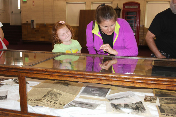 SHERRY VAN ARSDALL | THE GOSHEN NEWS<br /> Gabriella Umbower, 9, and Anna Umbower of Goshen, look at photos and newspaper accounts of the Palm Sunday tornadoes that occurred April 11, 1965. The display case is located inside the Elkhart County Historical Museum in Bristol.