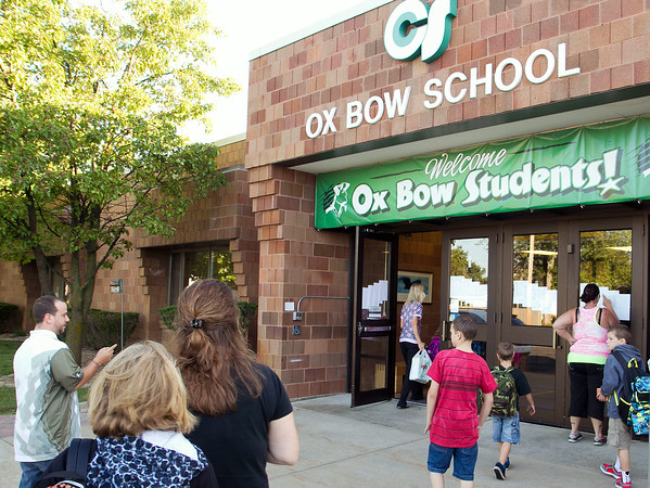 SAM HOUSEHOLDER | THE GOSHEN NEWS<br /> Parents and students walk into Ox Bow Elementary School Wednesday under a 'welcome back' banner for the first day of school. Concord and Middlebury school systems started Wednesday.