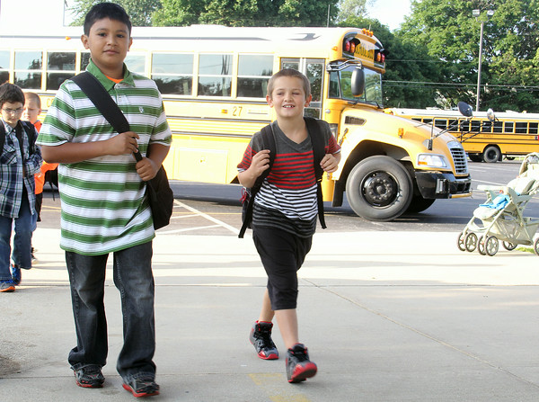 JULIE CROTHERS   THE GOSHEN NEWS<br /> Nappanee Elementary School students Oscar Martinez, fourth grade, and Tristen Robinette, first grade, walk from their bus toward the school Thursday on the first day of classes.