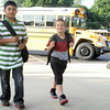 JULIE CROTHERS | THE GOSHEN NEWS<br /> Nappanee Elementary School students Oscar Martinez, fourth grade, and Tristen Robinette, first grade, walk from their bus toward the school Thursday on the first day of classes.