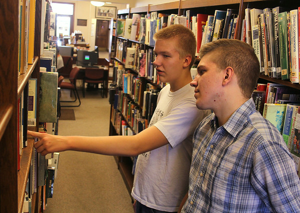 JULIE CROTHERS | THE GOSHEN NEWS<br /> Eric Park, 13, points out a book at the Syracuse Public Library to his brother, Connor Park, 22. Both said they prefer holding a book in their hand to reading on an e-reader.
