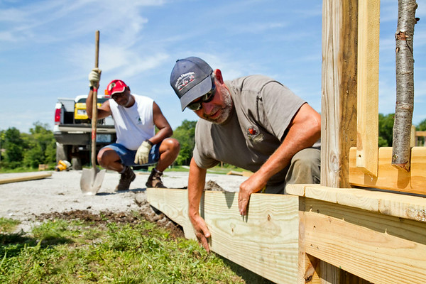 SAM HOUSEHOLDER   THE GOSHEN NEWS<br /> Goshen Parks Department employees Kevin Yoder, right and Ron Suggs, work on a platform at Mill Street Park Wednesday. The new Goshen park on the former Quality Drive-Away site does not have a completion date yet.