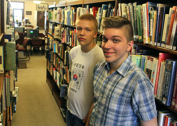 JULIE CROTHERS | THE GOSHEN NEWS<br /> Eric Park, 13, at left, and his brother, Connor Park, 22, frequent the Syracuse Public Library.Both said they prefer holding a book in their hand to reading on an e-reader.