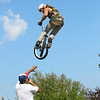 JOHN KLINE | THE GOSHEN NEWS<br /> Tyler Sparr of Pensacola, Fla., leaps over announcer Rich Hoppe during a professional BMX Jump Show by Solution Action Sports of Muncie at the Ligonier Marshmallow Festival Sunday.
