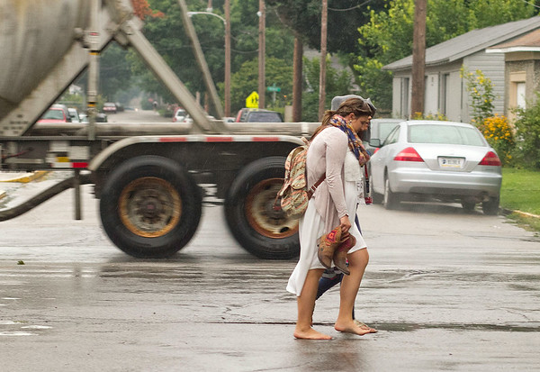 SAM HOUSEHOLDER   THE GOSHEN NEWS<br /> Goshen High School students Elizabeth Davidson, a sophomore and Jasmine Davidson, a junior, obscured, walk home Tuesday in the rain along Monroe Street.