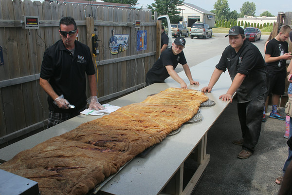 JOHN KLINE | THE GOSHEN NEWS<br /> Rulli's Italian Restaurant representatives, from left, Brock Nye, Brandan Weinley and Joseph Covello help guide a massive calzone as it exits the oven during a special fundraising event for the local Boys and Girls Club at the Middlebury restaurant Saturday afternoon.