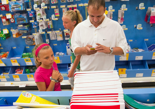 SAM HOUSEHOLDER   THE GOSHEN NEWS<br /> Richard Darling, right, consults his back to school list on his cell phone while daughter Kierstan, 11 and friend Destinee Bornkamp, 13, pick out supplies at Target Tuesday. The two girls will be attending NorthWood Middle School this fall.