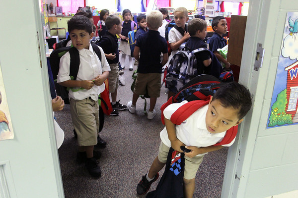 JULIE CROTHERS | THE GOSHEN NEWS Alex Perez, 5, peeks out the door of his kindergarten classroom Thursday afternoon at St. John the Evangelist Catholic School. Thursday was the first day of school for St. John's students.