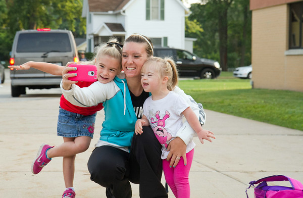SAM HOUSEHOLDER   THE GOSHEN NEWS<br /> Cassidy Fox, center, takes a photo with her daughters Jadyn, left who is beginning kindergarten at West Goshen Elementary School, and Kylie, 5, right. Goshen parents sent their children off to school Thursday for the first day of the 2014-2015 school year.