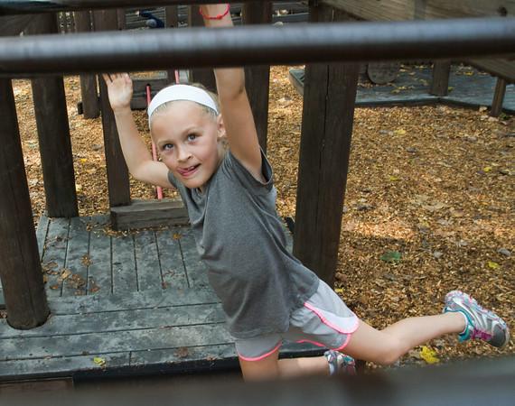 SAM HOUSEHOLDER   THE GOSHEN NEWS<br /> Anna Marinier, 7, Villa Park, Ill. climbs across monkey bars at Tommy's Kidz Castle in Shanklin Park Wednesday in Goshen.