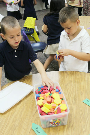 JULIE CROTHERS | THE GOSHEN NEWS<br /> Liam Post, 5, and his classmate Christian Lopez, 5, clean up foam shapes Thursday as their first day of kindergarten at St. John the Evangelist Catholic School draws to a close.