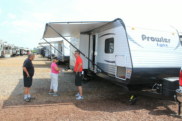 TOM AND CAROL STAMM of Scottsdale, Ariz. talk to Josh Mirowski, right, a salesman for Pete's RV Center of Schererville while they browse at the Midwest RV Super Show in Elkhart. The Stamms said they are looking for an RV to place at the Michigan property.