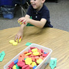 JULIE CROTHERS | THE GOSHEN NEWS<br /> Liam Post, 5, collects a pile of foam shapes Thursday during his first day of kindergarten at St. John the Evangelist Catholic School.
