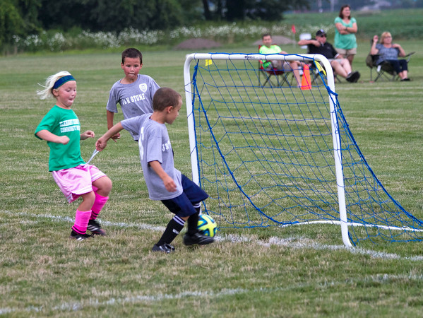 SAM HOUSEHOLDER | THE GOSHEN NEWS<br /> William Hahn, 7, scores a goal during a youth soccer game at the new Nappanee Soccer Complex. Hahn was assisted by teammate Dominic Freitas, 7, in the background and opponent Brooke Johnson, 6, right, is also on the play.