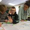 JAY YOUNG | THE GOSHEN NEWS<br /> Goshen Middle School sixth grades, from left, Daniel Edmonds, Preston Heeter and Briana Herrera Carranza discuss the imaginary country of Frontera during class on Tuesday afternoon. For the past six weeks, groups of sixth grade students have been creating make believe countries during their humanities classes. The students are responsible for developing everything from the landform, shape and natural resources each country possesses to the language and constitution each country abides by. On Tuesday, the students had a chance to view and leave feedback about their fellow classmates' countries.