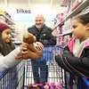 JAY YOUNG | THE GOSHEN NEWS<br /> Nine-year-old Diana Juarez, left, shows off a stuffed teddy bear she is considering buying to Ella Hubbard, 10, while Ella's father, Detective Bill Hubbard of the Goshen Police Department flashes a smile during the annual Shop with a Cop program Monday evening at Meijer.