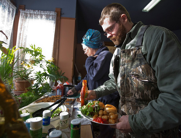 JAY YOUNG | THE GOSHEN NEWS<br /> Charles Hubbell, of Goshen, adds some salad dressing to his salad while Elkhart County Clubhouse board member Nanne Barkdull, of Goshen, scoops up some tater tots during a community meal at the house on Wednesday afternoon.