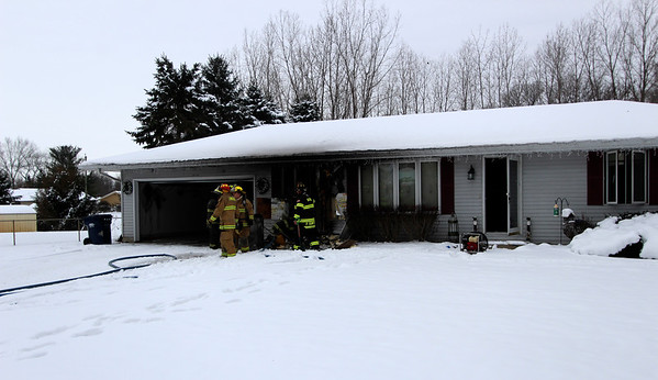 JOHN KLINE | THE GOSHEN NEWS<br /> Concord and Baugo township firefighters assess the damage during a house fire at 57011 Sequoia Drive on Goshen's west side early Friday afternoon.