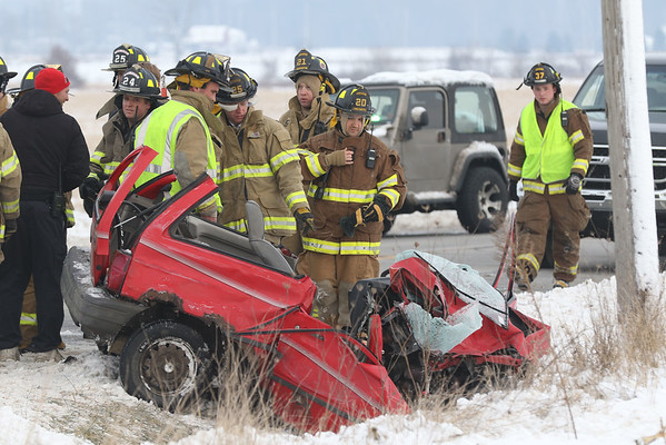 JAY YOUNG | THE GOSHEN NEWS<br /> Emergency workers look over what is left of a small red car after an accident near the intersection of U.S. 6 and C.R. 17 on Monday afternoon. Workers cut the top of the car off in order to extract the driver.