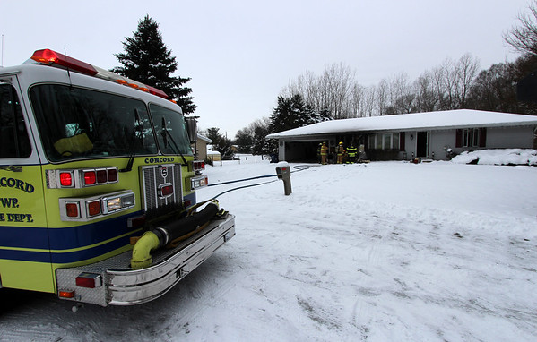 JOHN KLINE | THE GOSHEN NEWS<br /> Water hoses snake from a Concord Township Fire Department engine and tanker as Concord and Baugo township firefighters work a house fire at 57011 Sequoia Drive on Goshen's west side Friday afternoon.
