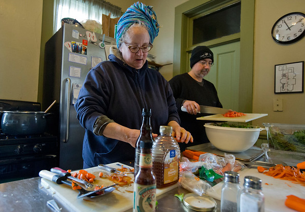 JAY YOUNG | THE GOSHEN NEWS<br /> Elkhart County Clubhouse board member Nanne Barkdull, of Goshen, slices carrots while Erich Miller, of Goshen, adds diced tomatoes to a salad as they prepare a noon community meal at the house on Wednesday afternoon.