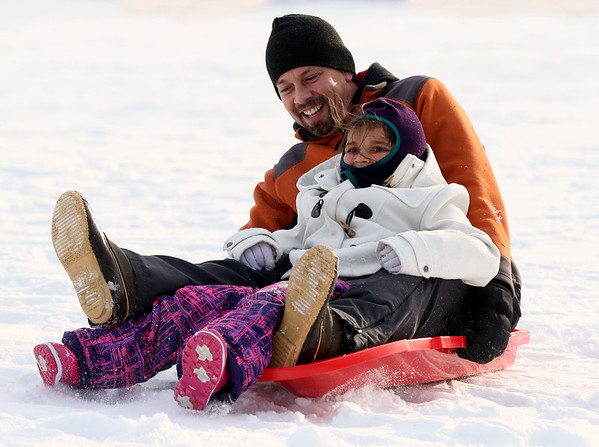 JAY YOUNG | THE GOSHEN NEWS<br /> Six-year-old Paiten Miller holds on tight as she sits in her father's lap, Lamar, while they slide down the hill in Abshire Park on Tuesday afternoon. Temperatures warmed up Tuesday afternoon after a bitterly cold Monday, allowing the pair to get out to the park and enjoy some sledding.