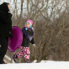 JAY YOUNG | THE GOSHEN NEWS<br /> Five-year-old Paige Miller flashes a smile as she looks back at her mom, Kasey, as the two hold hands while walking back to the top of the hill at Abshire Park on Tuesday afternoon. Tuesday saw higher temperatures after a bitterly cold Monday, allowing the pair to get out to the park to enjoy some sledding.