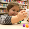 JAY YOUNG | THE GOSHEN NEWS<br /> Four-year-old Kayla Rodriguez giggles as she grabs a bottle of glue while creating a Christmas tree out of yarn Wednesday afternoon at the Goshen Public Library. Every day this week from 2 p.m. until 5 p.m. children are invited to the children's department at the library to create Christmas themed gifts. Tomorrow's project includes a star ornament and on Friday children will be making another Christmas tree, this time out of music note shapes. The event is free and open the public.