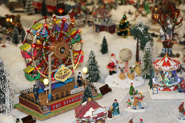 "SHERRY VAN ARSDALL | THE GOSHEN NEWS<br /> A ferris wheel complete with lights and music is part of the display of miniature homes and businesses with accessories that fill a third of the basement in the home of Jeff Ziegler of Wakarusa. He has been collecting pieces to set up the yearly village known as ""Zieglerville"" for 30 years."