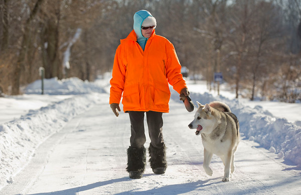 JAY YOUNG | THE GOSHEN NEWS<br /> Decked out in multiple layers of clothes, mittens and snow boots, Goshen resident Cindy Nodine  does her best to beat the cold despite temperatures hovering near zero as she takes her eight-year-old Alaskan Malamute named Atka for a walk along the Pumpkinvine Nature Trail near Abshire Park on Monday afternoon. Despite the sub-freezing temperatures, Nodine insists that Atka loves going for walks and playing in weather like this. According to meteorologist Mark Frazier of the National Weather Service, based in Syracuse, much of northern Indiana experienced record or near record lows on Sunday night. This included record lows of -9 in Fort Wayne and -14 in South Bend. Frazier explained that the cause of the unusually bitter cold temperatures the area is experiencing is due to an arctic high pressure system that has moved into and settled over the area. The weather service expects temperatures across northern Indiana to rebound in the coming days as the high pressure system moves on, with highs in the lower 30s by midweek and possibly higher by the holiday weekend.