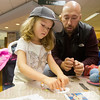 JAY YOUNG | THE GOSHEN NEWS<br /> Five-year-old Ella Schrock, of Goshen, pushes down as she glues wobbly eyes onto a paper snowman as her father Dennie watches Wednesday afternoon at the Goshen Library. The pair were taking part in the Library's Make It, Take It program running this week. Each day, crafts are available in the children's department.