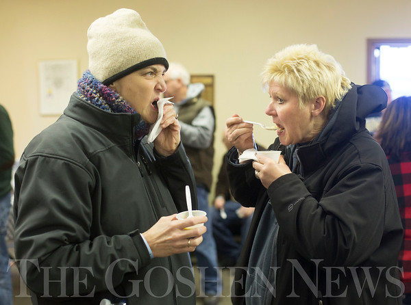 JAY YOUNG | THE GOSHEN NEWS<br /> Erin Johnson, left, and Babbett Ruby, both of Pleasant Lake, sample chili at the Chili Cook-Off in Shipshewana on Wednesday.  Johnson said the styles of chili were all very different and preferred the more traditional types of chili.