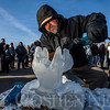 "JAY YOUNG | THE GOSHEN NEWS<br /> Onlookers gather around as Ryan Frauhiger carves a set of antlers for a mantelpiece during the annual Ice Festival in Shipshewana on Wednesday. Frauhiger, a wood carver by trade, said this was his first time carving ice. ""It's colder, but it cuts easier,"" Frauhiger said about the ice."